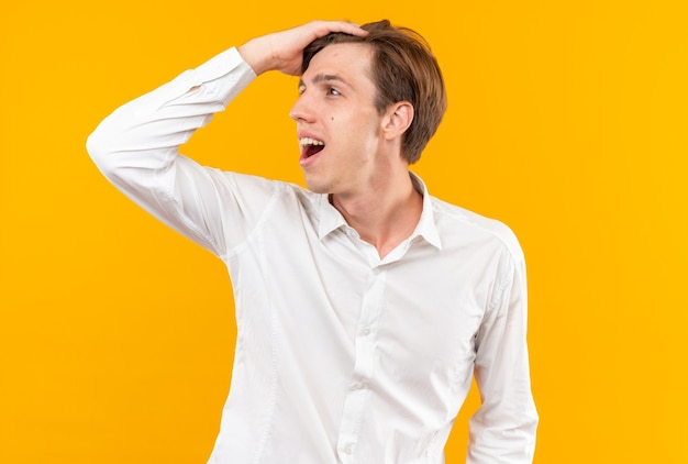 Glimlachend kijkende jonge knappe kerel die een wit overhemd draagt en hand op het hoofd zet, geïsoleerd op een oranje muur