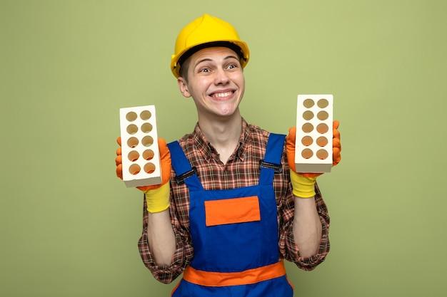 Glimlachend kijkende jonge mannelijke bouwer die uniform draagt met handschoenen die bakstenen vasthouden
