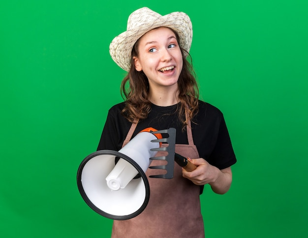 Glimlachend kijkende jonge vrouwelijke tuinman die een tuinhoed draagt en een luidspreker vasthoudt met een hark