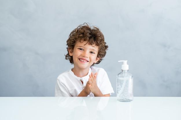 Glimlachend kind dat alcoholgel gebruikt voor desinfectie