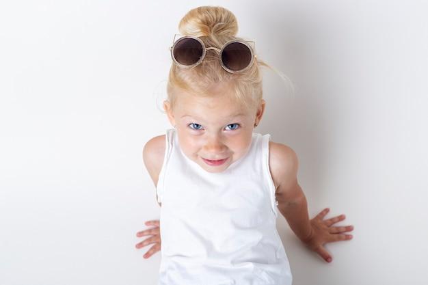 Glimlachend kind in zonnebril poseren op een lichte achtergrond in de studio.