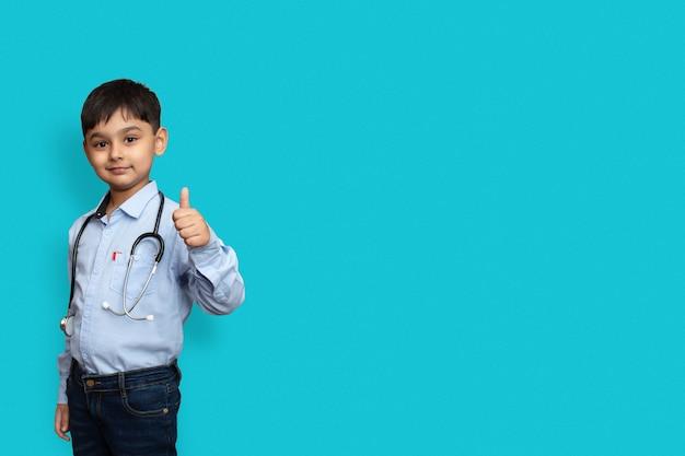 Glimlachend kind jongen arts met glazen effen achtergrond. mannelijke doc in wit overhemd doen thumbs-up. gezondheidszorg gezondheid geneeskunde concept. bespotten kopie ruimte