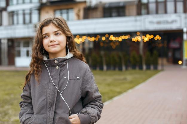 Glimlachend kindmeisje dat muziek luistert in de oortelefoons in de stad. ruimte voor tekst