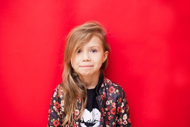 Glimlachend kindmeisje in modieuze kleding op rood
