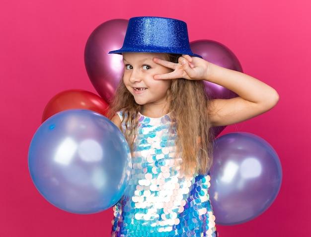 Glimlachend klein blond meisje met blauwe feestmuts met helium ballonnen en gebaren overwinningsteken geïsoleerd op roze muur met kopie ruimte