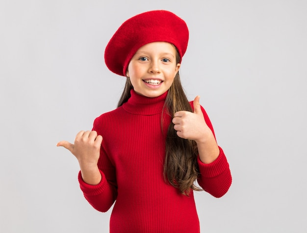 Glimlachend klein blond meisje met een rode baret die naar de zijkanten wijst en naar de voorkant kijkt geïsoleerd op een witte muur met kopieerruimte