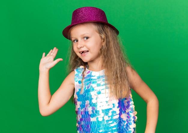 Glimlachend klein blond meisje met paarse feestmuts staande met opgeheven hand geïsoleerd op groene muur met kopieerruimte