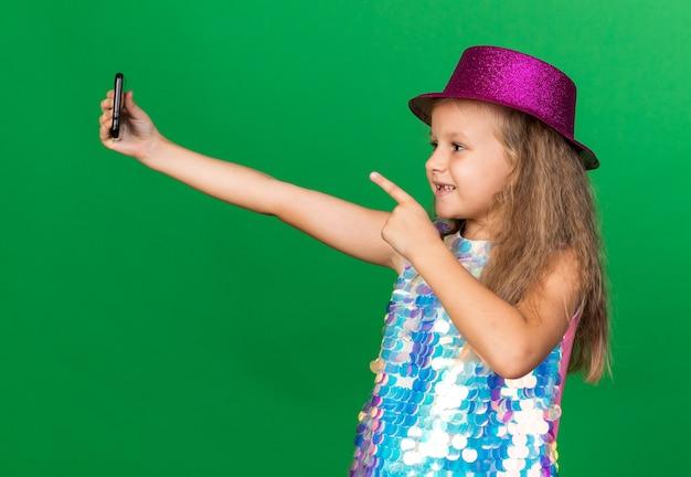 Glimlachend klein blond meisje met paarse feestmuts vasthouden en wijzend op telefoon nemen selfie geïsoleerd op groene muur met kopieerruimte