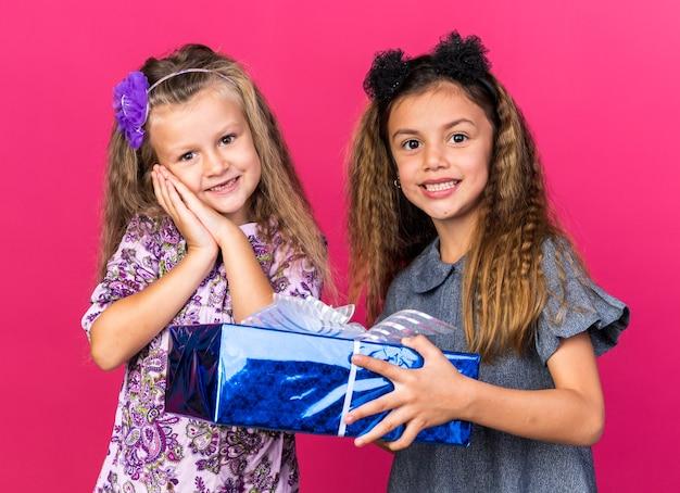 Glimlachend klein kaukasisch meisje dat een geschenkdoos vasthoudt en staat met een blij klein blond meisje geïsoleerd op een roze muur met kopieerruimte