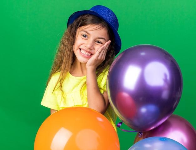 Glimlachend klein kaukasisch meisje met blauwe feestmuts die hand op het gezicht legt en heliumballonnen vasthoudt die op een groene muur met kopieerruimte worden geïsoleerd