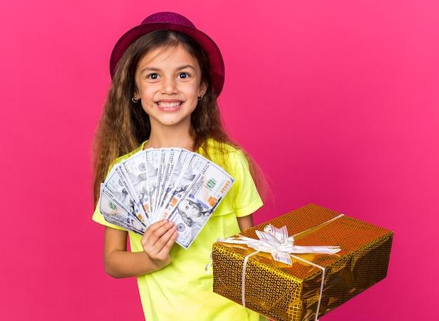 Glimlachend klein kaukasisch meisje met paarse feestmuts met geschenkdoos en geld geïsoleerd op roze muur met kopieerruimte