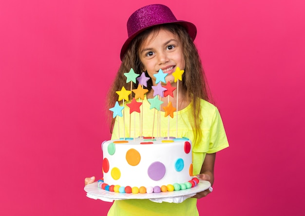 Glimlachend klein kaukasisch meisje met paarse feestmuts met verjaardagstaart geïsoleerd op roze muur met kopieerruimte