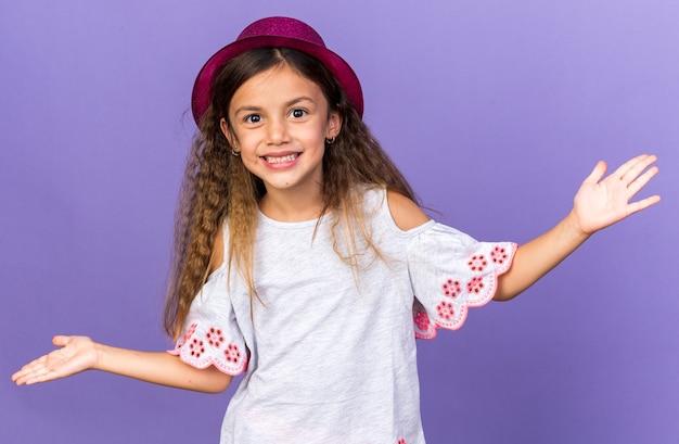 Glimlachend klein kaukasisch meisje met violet feestmuts dat handen open houdt geïsoleerd op paarse muur met kopieerruimte