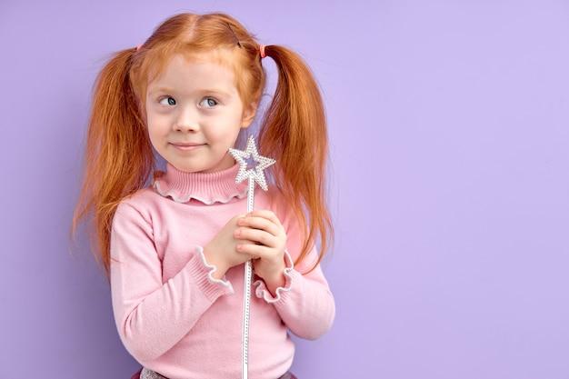 Glimlachend klein meisje dat toverstaf in de hand houdt, wil tovenares zijn, schattig schattig meisje met natuurlijke rode haardromen die wegkijken, sprookjesspel. kostuum feest