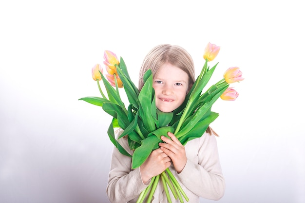 Glimlachend klein meisjeskind zonder voortanden die kleurrijke boeketten van tulpenbloemen op een wit oppervlak houden