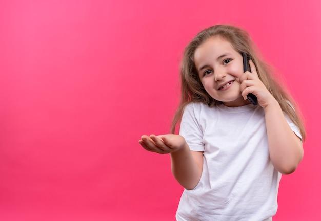 Glimlachend klein schoolmeisje dat een wit t-shirt draagt, spreekt over de telefoon die op geïsoleerde roze achtergrond hand wordt uitgestoken om door te sturen Gratis Foto