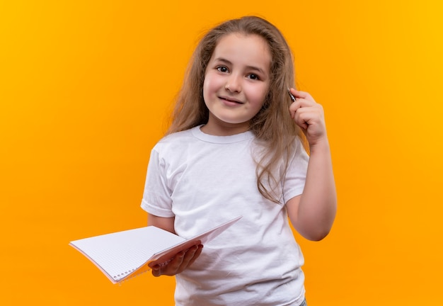 Glimlachend klein schoolmeisje die het witte notitieboekje en de pen van de t-shirtholding op geïsoleerde oranje achtergrond dragen