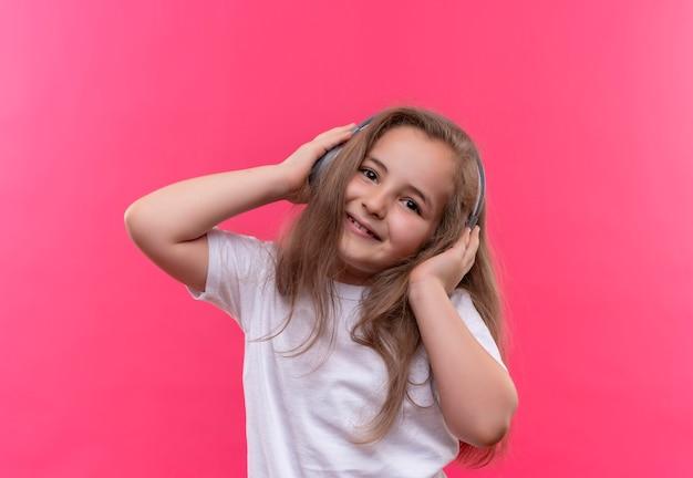 Glimlachend klein schoolmeisje die wit t-shirt dragen luistert muziek uit hoofdtelefoons op geïsoleerde roze achtergrond