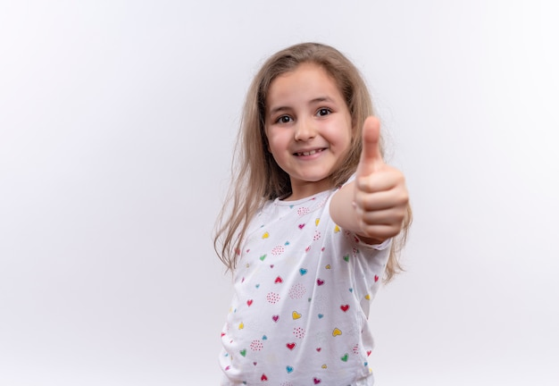 Glimlachend klein schoolmeisje die witte t-shirt dragen haar tumb omhoog op geïsoleerde witte achtergrond