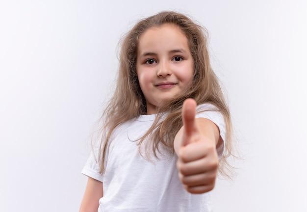Glimlachend klein schoolmeisje die witte t-shirt met haar duim omhoog op geïsoleerde witte achtergrond dragen
