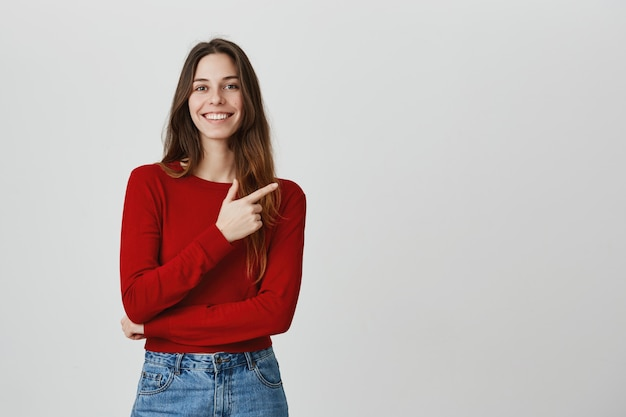 Glimlachend knap meisje die vinger rechtsboven op promobanner richten