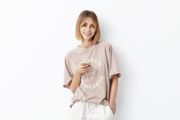 Glimlachend knap vrouwelijk model met geknipt kapsel dat alleen loopt, met oortelefoons en mobiele telefoon om zichzelf te vermaken