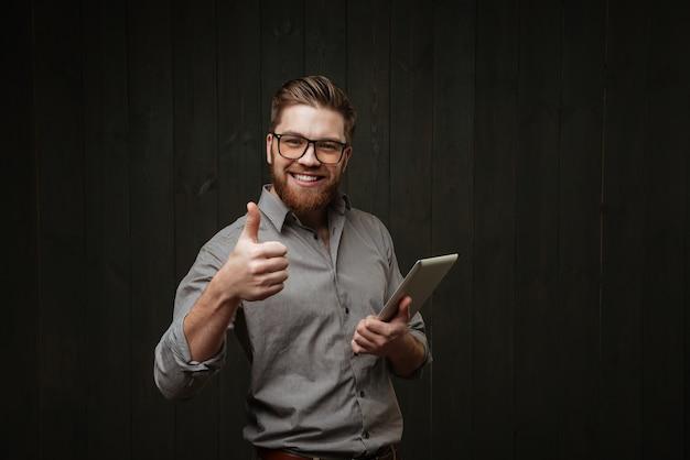 Glimlachend knappe jongeman met behulp van tablet en duim opdagen geïsoleerd op een zwarte houten oppervlak