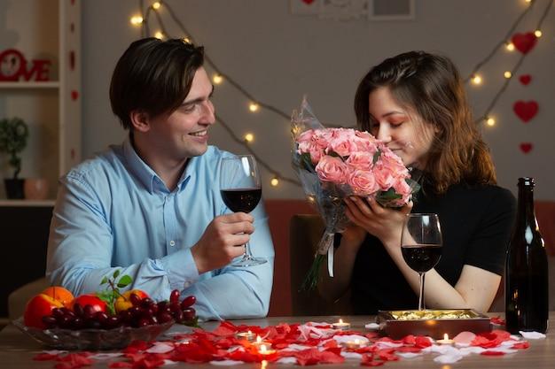 Glimlachend knappe man met glas wijn en kijken naar mooie vrouw snuiven boeket bloemen zittend aan tafel in de woonkamer op valentijnsdag