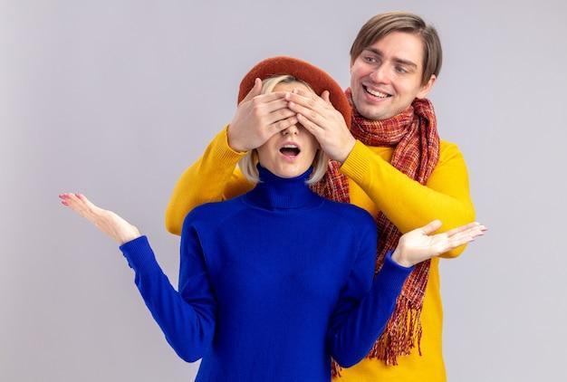 Glimlachend knappe slavische man met sjaal om zijn nek ogen sluiten van verrast mooie blonde vrouw met baret op geïsoleerde op witte muur met kopie ruimte