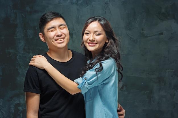 Glimlachend koreaans paar op grijs