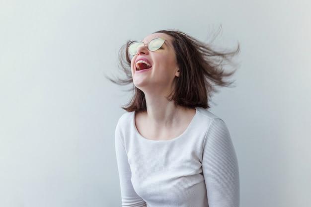 Glimlachend kortharig donkerbruin meisje in trendy gele zonnebril die op wit wordt geïsoleerd