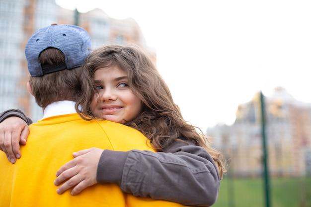 Glimlachend krullend donkerbruin meisje dat haar oudere broer knuffelt tijdens het spelen op de sportwerf