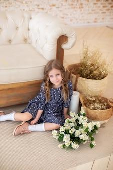 Glimlachend krullend haired meisje met een boeket van jasmijnbloemen