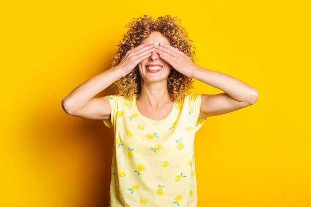 Glimlachend krullend meisje bedekte haar ogen met haar handpalmen op een gele achtergrond