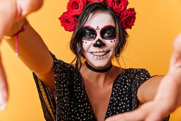 Glimlachend krullend meisje met donker haar poseren. selfiemodel met buitengewone make-up op geïsoleerde muur