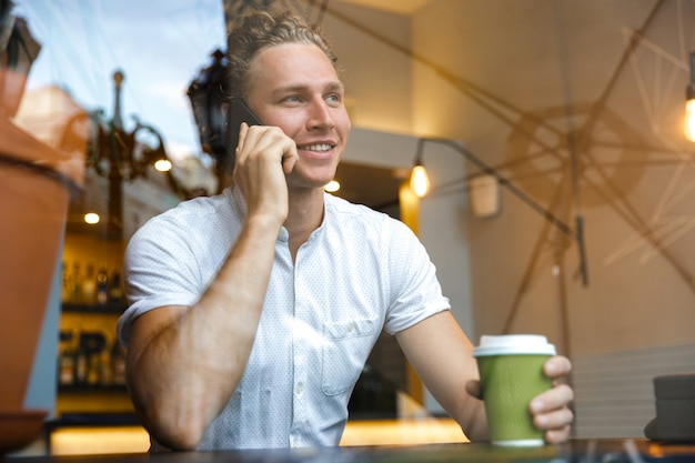 Glimlachend krullend zakenman praten door de smartphone en koffie drinken zittend aan tafel in café