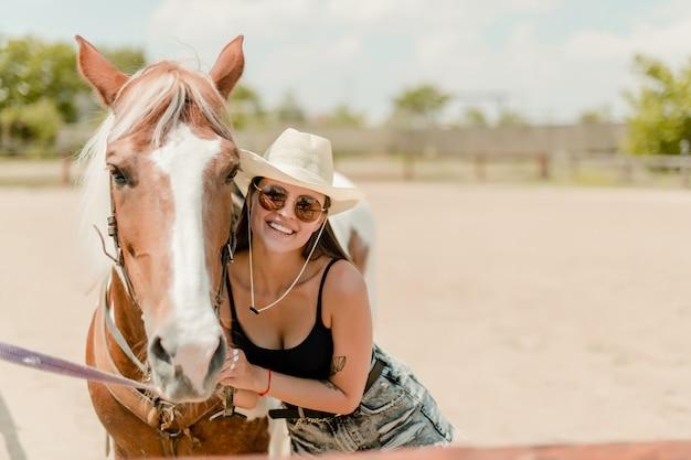 Glimlachend landmeisje in cowboyhoed met haar paard op een boerderij