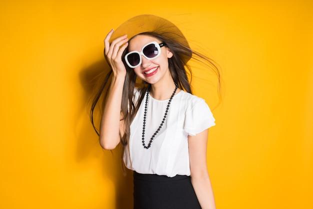 Glimlachend langharig meisje in hoed en zonnebril poseren op gele achtergrond