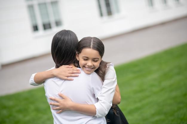 Glimlachend leerplichtige meisje met gesloten ogen moeder strak knuffelen op schoolplein