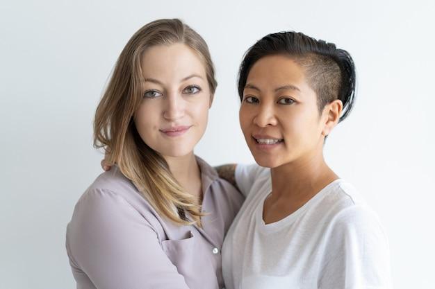 Glimlachend lesbisch paar die en camera omhelzen bekijken