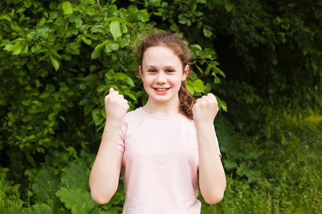 Glimlachend leuk meisje die haar vuist dichtklemmen die ja gebaar maken terwijl status in park