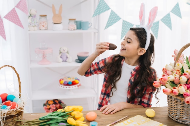 Glimlachend leuk meisje met konijntjesoren boven haar hoofd die chocoladepaasei eten