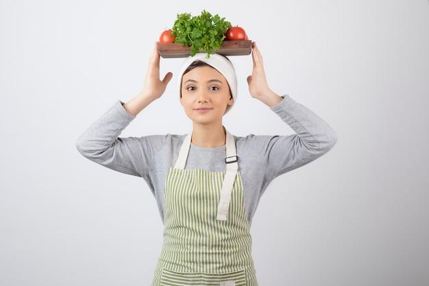 Glimlachend leuk vrouwenmodel dat een houten plank met verse groenten op hoofd houdt.