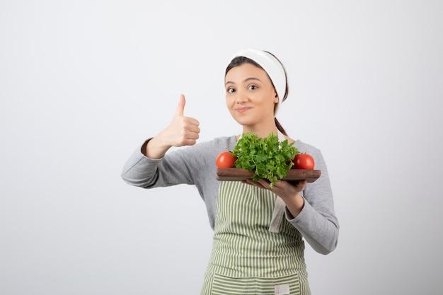 Glimlachend leuk vrouwenmodel met een houten plank van verse groenten die een duim tonen.