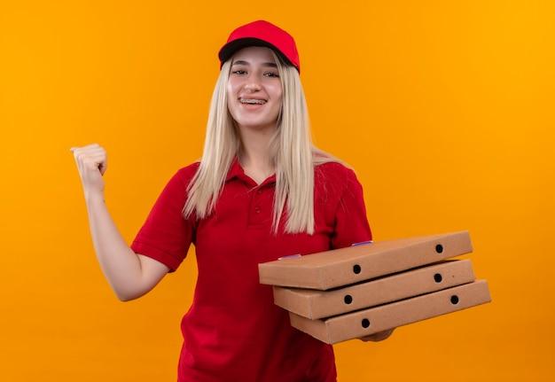 Glimlachend levering jong meisje dat rode t-shirt en pet draagt die pizzadoos toont die ja gebaar op geïsoleerde oranje achtergrond toont