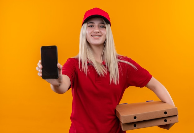 Glimlachend levering jong meisje die rode t-shirt en glb dragen die pizzadoos houden en telefoon tonen bij camera op geïsoleerde oranje achtergrond