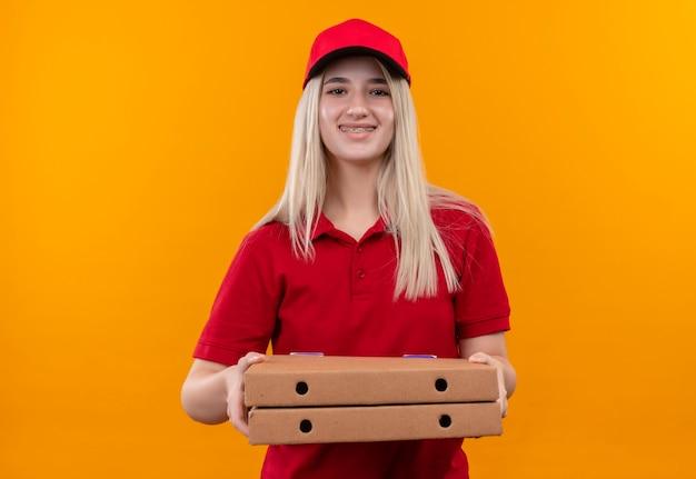 Glimlachend levering jong meisje die rode t-shirt en pet in de pizzadoos van de beugelholding op geïsoleerde oranje achtergrond dragen