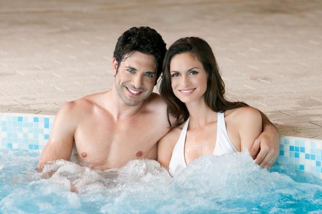 Glimlachend liefdevol paar samen ontspannen op een jacuzzi in de spa