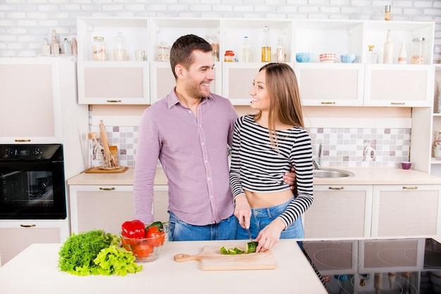 Glimlachend liefdevol paar snijden komkommers voor salade in de keuken