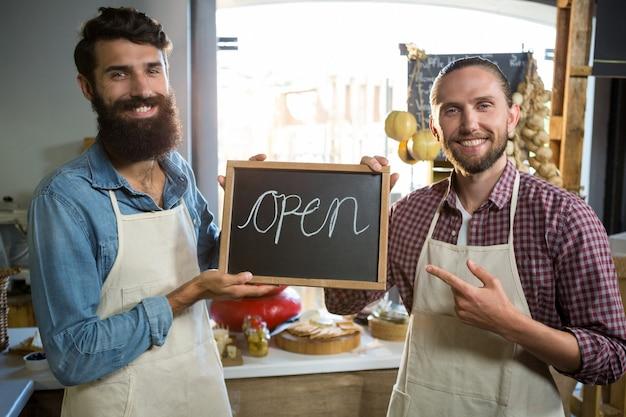 Glimlachend mannelijk personeel dat een open teken houdt